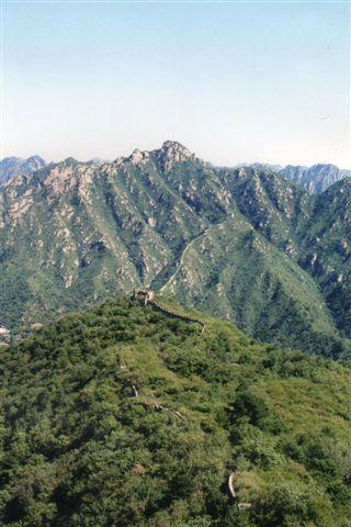 Den kinesiske Mur har strengt taget aldrig forhindret erobrere i at overtage Kina. Der var dog dynastier, fra Mongoliet og Manchuriet. hvor muren lå midt i Kina og nærmest var i vejen. Den forfaldt derfor, men som hisrorisk minde er en del kilometer genopbygget rundt om i Kina. Her står jeg ved den genopbyggede murs ende vest nordøst for Beijing og skuer ud over den ikke restaurerede del, der strækker sig så langt øejet rækker også over bjergene i baggrunden. Jeg gik også på den urestaurerede mur, indtil jeg på en tjørnebusk rev mine busker. Foto fra 1999.