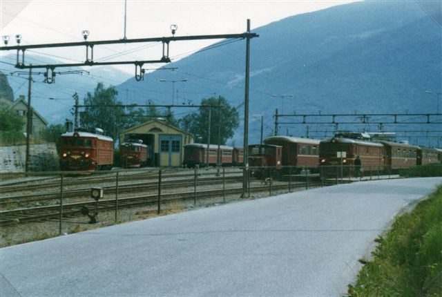 På jernbanestationen i Flåm holder en morgen alle tre ellokomotiver samt en akkumulatorrangermaskine. Uden for synsfeltet holdt nogle motorvejssæt, så banen var rustet til krydstogtturister. Foto fra 1983.