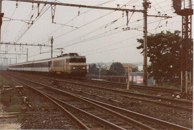 SNCF BB 7381 ned 6-vogntog til Strassbourg. Man ser et langt midliggende overhalingsspor samt et af to inustrispor. Bemærk stangtrækket til skifterne og signalerne til industrisporene.