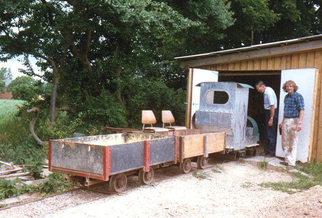 Det endnu umalede lokomotiv uden for remisen sammen med to arbejdsvogne. Foto: Svend Guldvang 1989.