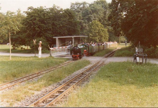 Minitoget passerer et bomanlæg i normalstørrelse. Vi er på den del af banen, der i praksis er dobbeltsporet. Personen forekommer stor i forhold til lokomotivet.