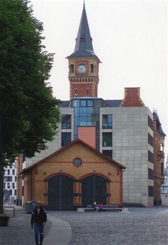 2010 var jeg igen på Rheinauhafen, men nu for at se på arkitektur. Smukt restaurerede gamle bygninger, som havnens gamle remise. I baggrunnden en administrationsbygning, der vil noget. Tårnet tilhører ikke en kirke, og det er ikke Big Ben.