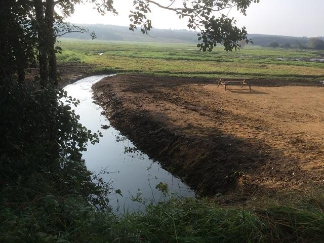 Gennem engen en å sig slynger. I de år jeg har boet i området, har åer og bække løbet den nærmeste vej til havet, og to steder var åen endog stemmet op til dambrug og vandmøller. Ikke desto mindre var der i bækkene både niøjne og ørreder. I 2015 indviedes et naturområde her. Opstemningerne er fjernet og erstattet af en stryg med stensatte sider og stærk strøm. Desuden nye, slyngede bækløb gravet. Det er nu muligt for også havørreder at gå op og yngle her, som de gør i en beskeden nabobæk. Desuden skulle det nye vådområde optage store mængder af drivhusgassen kultveilte. Billedet viser den nyslyngede bæk.