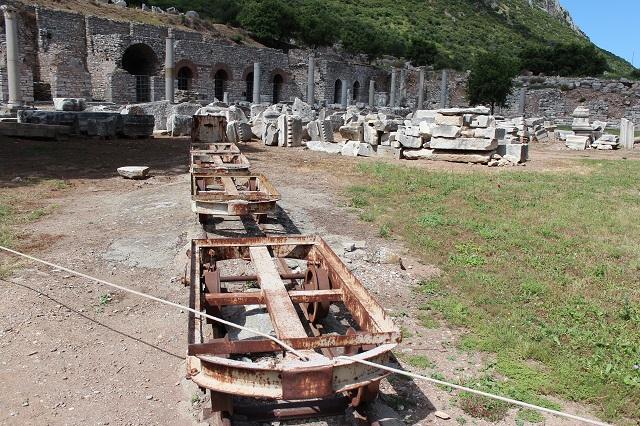 En hel række af smalsporvogne opstillet midt i ruinbyen. 2014.