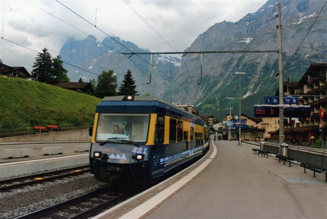 BOB 421 var godt nok en styrevogn, men af mere moderne type medlavgulvsdel. Stationen ses for enden af sporet. Til højre Wengernalpbahns spor, der er har tyve centimeter mindre sporvidde. De tre trekanter på motorvognen symboliserer de markante bjerge i Berner Oberland: Jomfruen 4158 meter, Munken 4099 meter og Uhyret, 3970 meter. Området vartegn. I baggrunden roden af Schreckhorn 4078 meter og Wetterhorn 3701 meter. 2012.