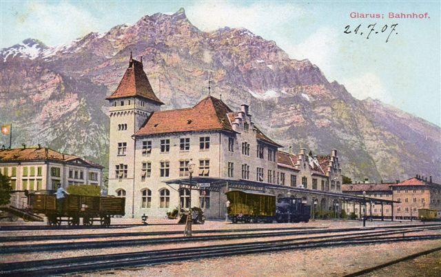 Grarus 517. Glarus i kantonen af sammen navn ligger nordvest for Chur. Stationen ligger på en normalsporet statsbane. Et damplokomotiv og et par godsvogne ses. Postkort købt 1907.