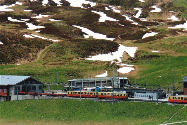 To af de ældre togsæt ved remisen. Hele gedemarkedet på Jungfraujoch skulle forsynes med alt lige fra mad, souvenirs og drikkevand med banen. Disse tog fremførste normalt af de ældre motorvogne. Det anderledes farvede materiel er WABs. Mundingern til vendetrekanten inde i bjerget ses. Del skulle maskinen være nederst på faldet, og dels var sæderne indrettet med rygstøddets hældning til kun at køre på en bjergside. Der var vendetrekant i Grund og her i Kleine Scheidegg. 2012.