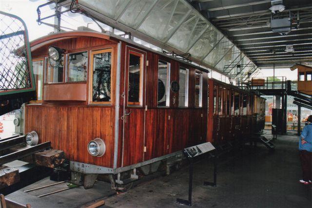 På trafikmuseet i Luzern stod JB 1, der oprindeligt var bygget efter Rowansystemet som Gribskovbanens dampvogne. Som den står her, er den dog ombygget til lokomotiv. Vognen bag lokomotiver er også fra JB, men det tredje køretøj i rækken er fra en anden bane. Lokomotivet her har to bøjler på hver strømaftager, og krævede altså to parallelle overledninger. 2012.