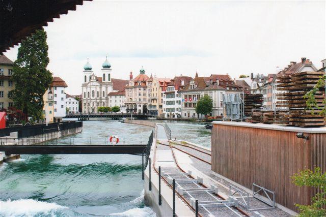 Gennem Luzern løber Rhinbifloden Reuss. Dels skal anlægget her tjene mod beskyttelse af byens lavere dele mod oversvømmelser, dels har de været udnyttet vandkraft her siden 1278. På sporene kører en kran, der til daglig holder i remisen. Kranen sætter højvandsreguleringer i floden, når det er nødvendigt. Foto fra 2012.
