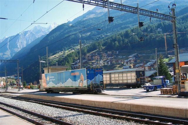 En Migros-containervogn på godspladsen. Fornødenhederne kommer men banen! Migros svarer vel nærmest til Irma eller Brugsen. En af byens mange elbiler ses også på pladsen. 2009.