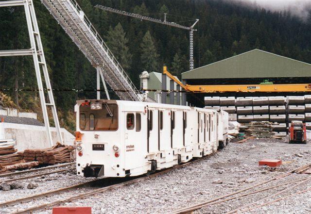 Foruden adskillige tunneler på Gotthardbanen bygget af endnu flere firmaer, byggedes også en genvej for Räthische Bahn, Vereinatunnelen, der byggedes fra både nord og syd. Her ArGe Vereinn Nord i Klosters ses Schöma 5023/1989. Det er motovognen i bag. Forrest en styrevogn. Sættet startede ved Storebæltstunnelen som MTG 35-06, kom derefter til Kanaltunnelen som TML RU 006 A + B. I Klosters ses ikke noget nummer. Sættet bruges til mandskabstransporter. I baggrunden tunnelelementer. Foto Ulrich Völz 1995. Negativ 627/24.