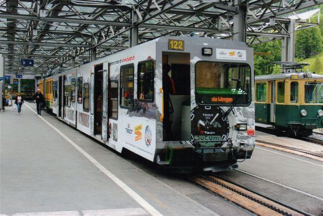WAB 122 var reklamefolieret. Til højre en ældre vogn, der mest brugtest af banetjenesten. Lauterbrunnen 2012.