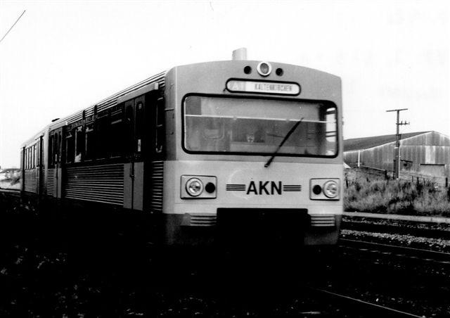 AKN VT2.31 krydser orlovstoget i Boostedt 1986. Disse moderne togsæt kørte sjældent nord for Kaltenkirchen, men som det ses her, hændte det. Formentlig var toget udstyret med både el og diesel. På det første stykke af banen i Hamburg kørte S-banen og AKN på samme spor med tredjeskinne til strømforsyning. under et kort stop på vejen startedes dieselmotoren, og toget forstsatte uden strømskinne.
