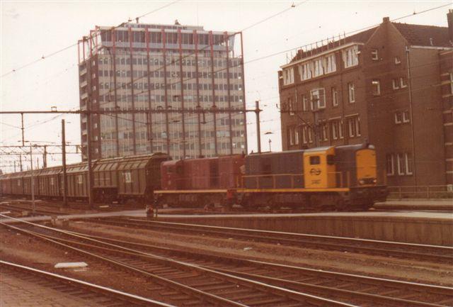 To NS-diesellokomotiver af 2400-serien forspændt en halv snes selvtømmende fireakslere mærket VAM Compost og tilhørende Amsterdams Kommune.