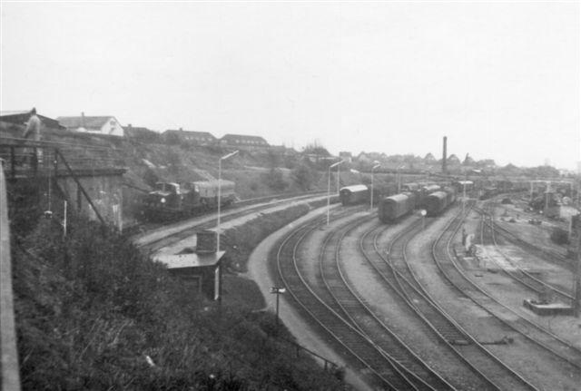 Efter stationene stig Havnebanen fremdeles og passerer på Bro C Nordgånde spor med et særtog med to Mh og en undervisningsvogn samt banen fra spor 5 til Rangerbanegården. Til højre personvognaristen. Foto: Bent Hansen 1968.