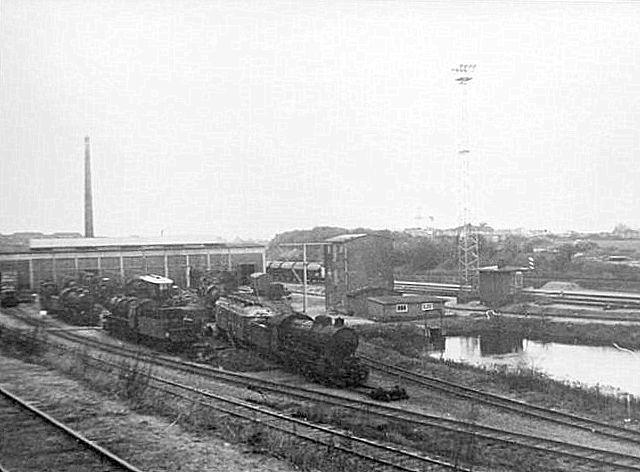 Remisen med hensatte damplokomotiver og en enkelt Mp-vogn. I forgrunden et vandreservioer af oppumpet vand fra en bæk under opfyldet. Den høje bygning ved søen er et vandtårn. Post 3 er endnu intakt! Foto: Bent Hansen 1968.