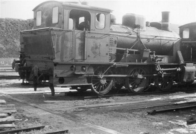Høj F på lokomotivkirkegården nord for remisen. Den type var en togmaskine i modsætningen Fredericias F-maskiner, der var rangerlokomotiver. De kørte i Sønderjylland, sidst på Åbenråbanen. Den har fåret afmonteret dele af gangtøjet i forbindelse med transporten. Desværre er det eneste lokomotiv, jeg fotograferede, sikkert fordi der var masser af andre mere gængse typer. Foto: Bent Hansen 1962.