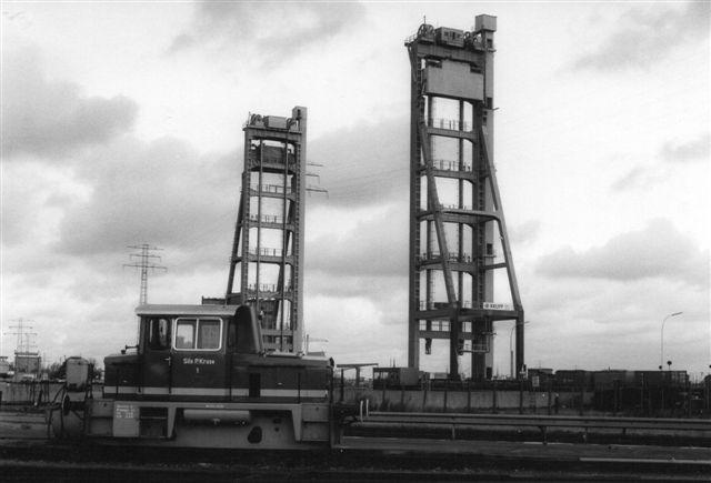Kruse 1 med Rethebroen som baggrund. På havnen fandtes en del klapbroer og to hævebroer, hvor vej- og baneforløbet hævet ved hjælp af de to elevatortårne, så et skib kan passere under. 1986.