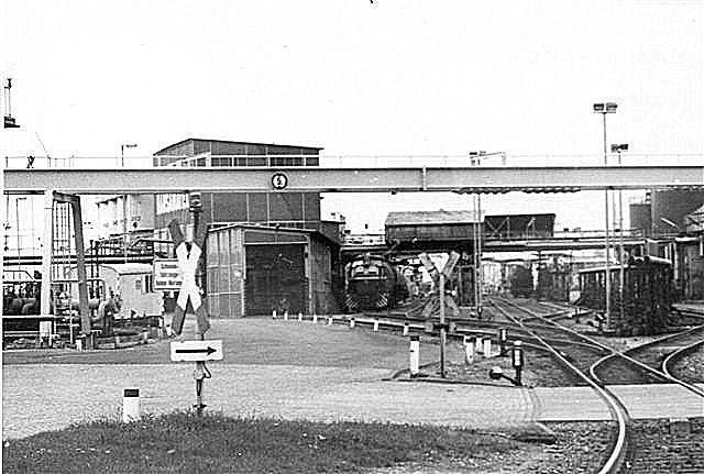 Når jeg her har fotograferet ind på anlægget, skyldes det, at en lastbil dækkede mig, så portvagterne ikke så mig. Et lokomotiv holder i remisen til venstre og til højre for remisen holder endu et lokomotiv. Foto 1987.