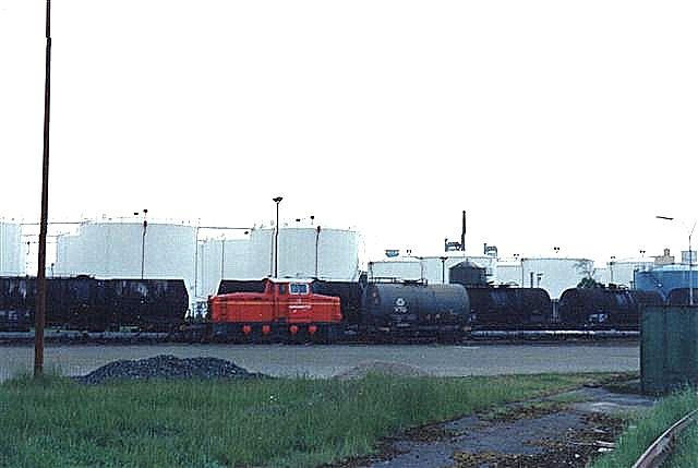 1990 lykkedes det i regn og modlys at fotografere ind over hegnet fra ladet af en lastbil. der er både modlys og regndis. Lokomotivet er Hansamate 2, Deutz 57707/19??. Lokomotivet er mærket med et V, der imidlertid ikke ses her. Foto 1990.