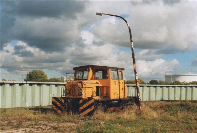 2003 stod lokomotivet ved HJM Hafenumschlagsbetriebe og så noget brugt ud. Fotografen Jochim Rosental har ikke angivet nogen adresse. Hegnet er en beskyttelsesmur mod højvande.