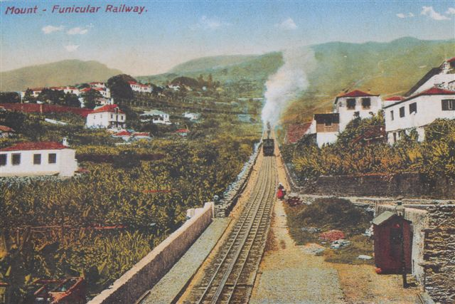 Affoto af postkort (tidligt farvefoto/håndcoloreret?) af banen med tog ved en af mellemstationerne. Ukendt tidspunkt.