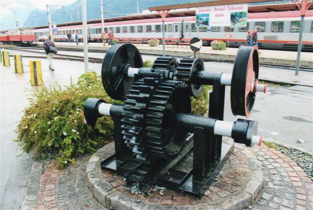 """Som nævnt ligenede banen på Madeira meget Achenseebahn i Østrig. Her ses en tandhjulsskulptur i Jenbach. Der er noget mere """"bid# i disse tandhjul end i tandhjulene på Madeiraskulpturen. Der findes dog også tyndere tandhjuls i Riggenbachsystemet beregnet til to eller tre forskudte tandstænger med tilsvarende tyndere tandhjul. Foto 2013."""