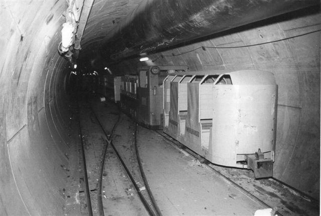 En mandskabsvogn og lokomotiv uden nr, SIG 709744/1979 sammen med andet materiel i tunnelen. Foto: Ulrich Völz 1986.