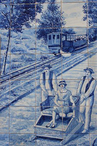 Her er først et tog på kakler placeret med andre historiske kakkelbilleder på Café Ritz. Ved siden af en af slæderne, der kører turister ned fra Monte. Foto 2016.