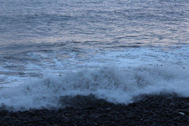Rullestene på stranden kastedes rundt. De ses som de sorte prikker i skummet. De kastedes helt op på stien langs kysten.