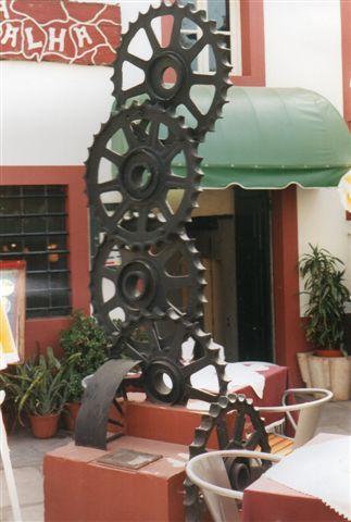 Foto af tandhjulsskulpturen nu omgivet af fortovscafeer. 1999.