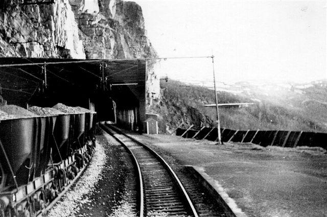 """Katterat krydsningsstation. Banen havde på en bro lige passerert en slugt og kørte nu ud på denne """"hylde"""" på den lodrette fjeldside, hvor der lige var plads til en station og to spor. Efter stationen gik banen ind i fjeldet først i i et galleri så i tunnel. Malmvognen er af ældre model, men allerede dengang treakslede. Foto: S. Thostrup-Christensen 1969."""