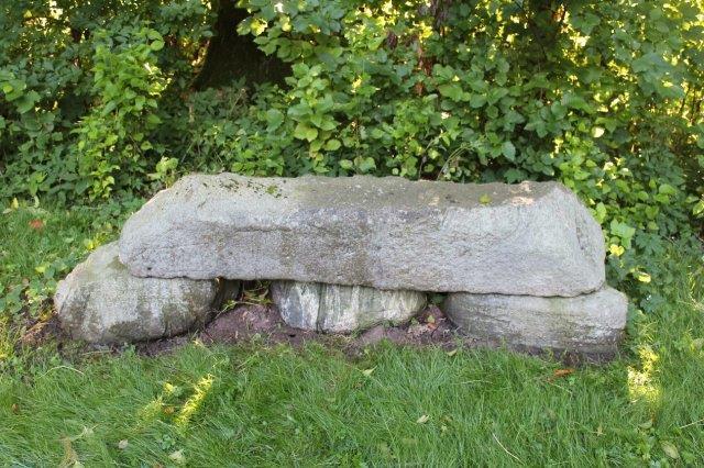 Stenen ligner mest en havebænk, og man skal se godt efter, for at få øje på runerne samt på teksterne på de to yderste bæresten.