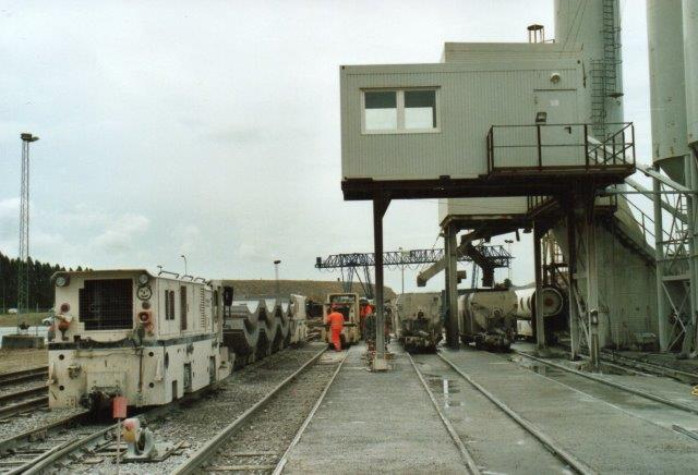 Udsigt over banegården ved mørtelanlægget lige inden tunnelen. Toget består ef tre elemntvogne og en mørtelvogn. Flere mørtelvogne og en betonkanon holder på læssesporene. Lokomotivet med smileyen er MCG 1. 2007.