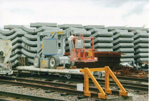 Et lang fladvogn læsset med en mobil liftvogn. 2007.