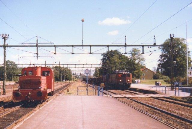 Vor maskine har krydset hovedsporene Stockholm - Göteborg og afventer nu rangertilladelse. Imens raser et godstog fremført af SJ Ma 873 genne stationen. 1986.