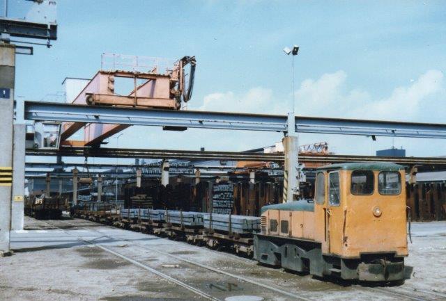 Halmstad Järnvärks AB 13 med sit tog med jernbarer på lagerpladsen.