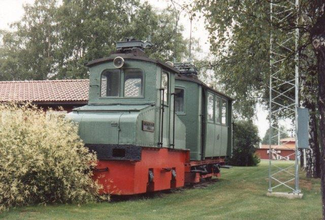 Stora Kvarnsveden havde tidligere en tre kilometer bane til Borlænge i 693 mm sporvidde. Herfra er lok 1 bevaret. Det var en AEG fra 1902. Bagved ses noget, de lærde er uenige om. Enten et motorvogn til personbefordring eller en personvogn med strømaftager til elvarme. Vi kiggede ind og konstaterede håndtage til fartregulering? 1988.