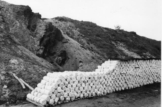 De tørrede, pressede cylinderformede blokke, som afsattes fra fabrikkerne. I væggen i baggrundes et sandlag sammenkittet af jernholdige forbindelser.