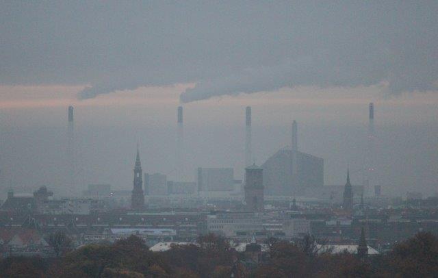 """Udsigten fra Edits stue varierer fra sommer til vinter og fra morgen til aften. En morgen omkring første november var Amagerværkets skorstene delvist skjulte af skyer, mens toppe var over skyerne. Til gengæld kreerede de så nye skyer højere oppe.Det så sådan ud. Vi ser den nye """"skibakke"""" på Amagerværket sammen med Københavns Domkirke og Vor frelsers Kirke, den med den udvendige vindeltrappe."""