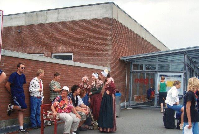 En dag i 2009, hvor vi ventede på tog, tog jeg et foto af min rejsefælle. Tilfældigvis kom nogle kvinder i frisiske nationaldragter med på billedet. Anledningen kendes ikke, for normalt går de ikke i nationaldragt. På Föhr tager det over to timer at iføre sig en kvinde-fest-dragt, og ofret kan ikke gøre det alene, men skal have hjælp.